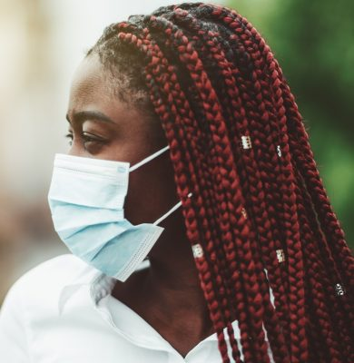 Close-up portrait of a young African woman with chestnut braids and in a virus protective mask over her face; masked black woman outdoors - protection against influenza and pandemic, selective focus